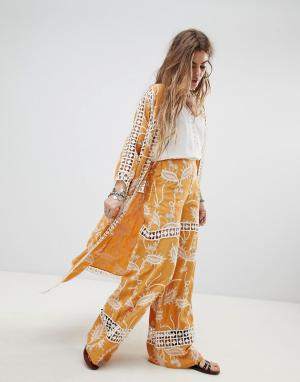 Native Rose Расклешенные брюки с кружевными вставками. Цвет: желтый