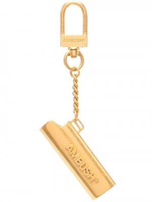 Брелок в виде футлра для зажигалки с тисненым логотипом AMBUSH. Цвет: золотистый